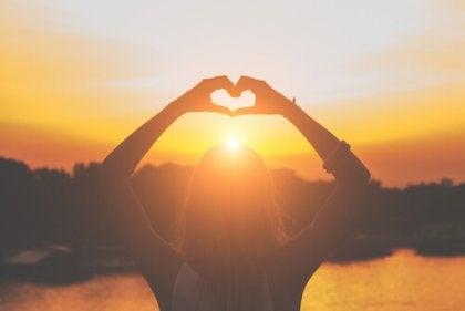 Manos haciendo un corazón al amanecer