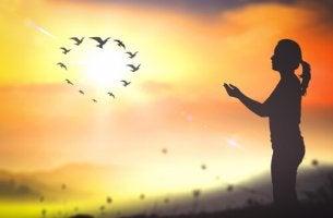 Mujer con las manos levantadas y un sol rodeado de pájaros