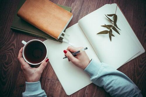 Mujer escribiendo y tomando café