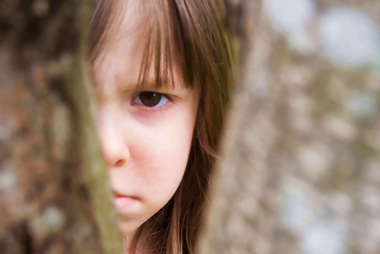 Cara de niña enfada detrás de un árbol