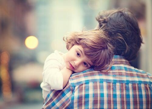 Niño cogido en brazos por su padre