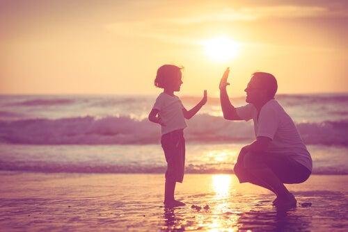 Padre chocando la mano con su hija en la playa