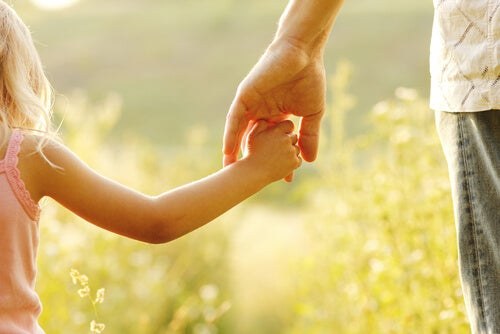 Padre e hija agarrados de la mano