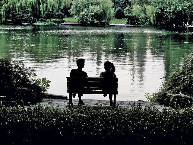 Pareja sentada en un banco separada