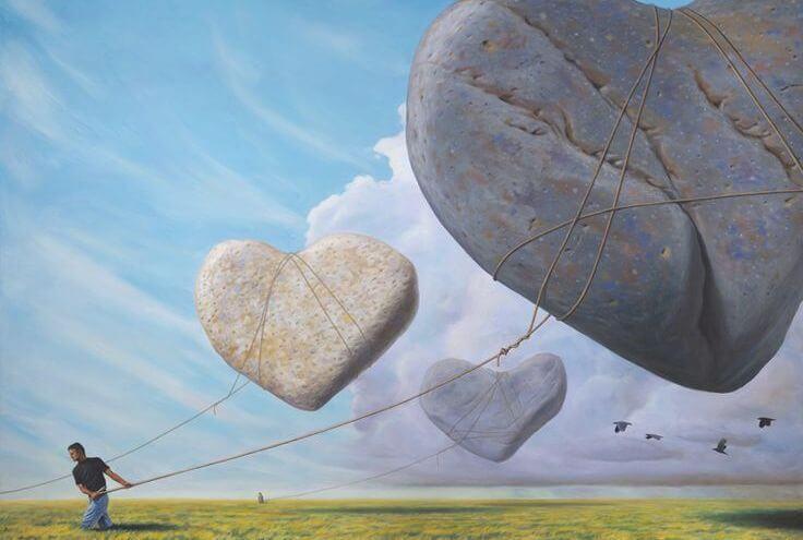Hombre tirando con una cuerda de unos corazones de piedra