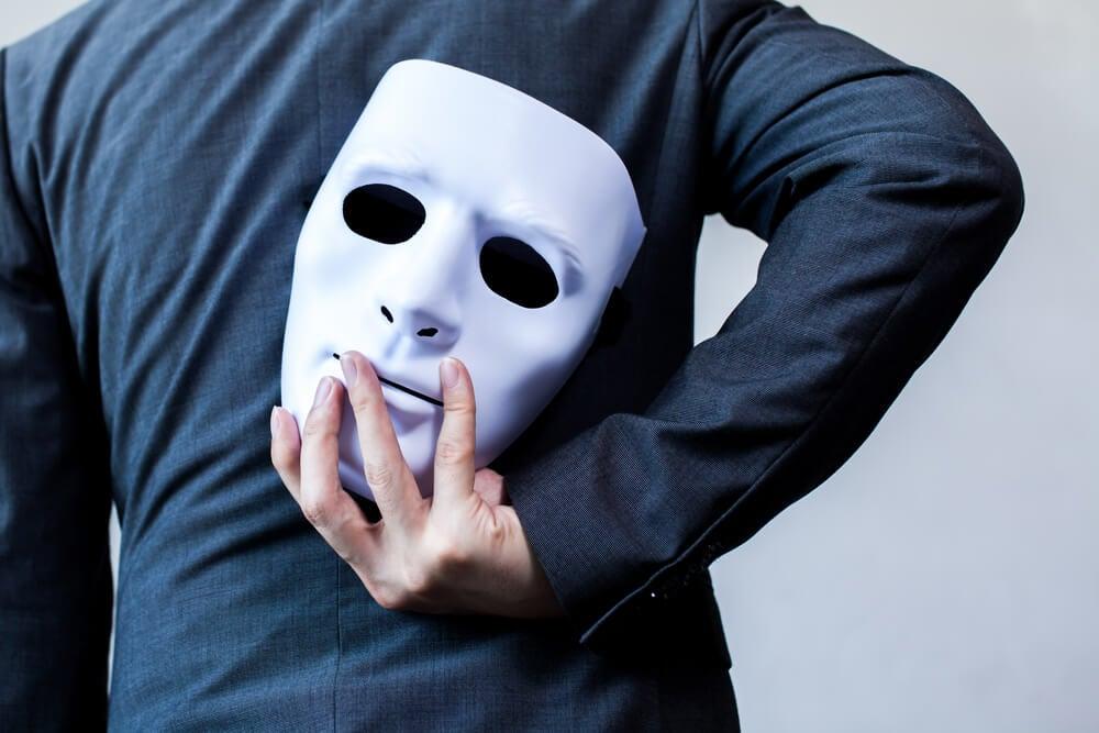 Hombre con máscara a sus espaldas