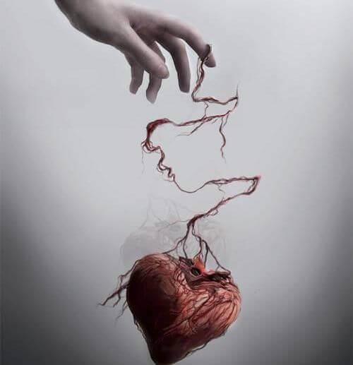 Mano sujetando corazón maltratado