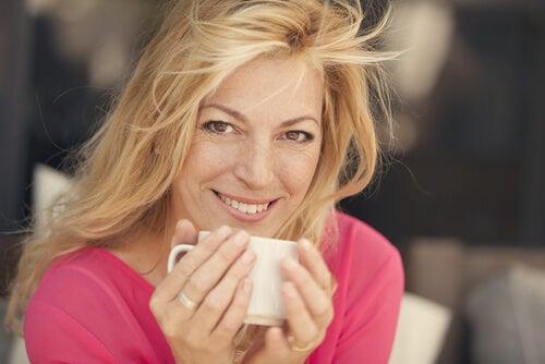 Mujer de cuarenta tomando café simbolizando cómo ser más felices después de la mediana edad