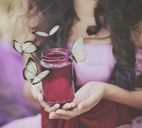 Mujer con un tarro de cristal y mariposas