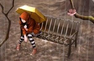 Mujer preocupada sentada bajo la lluvia
