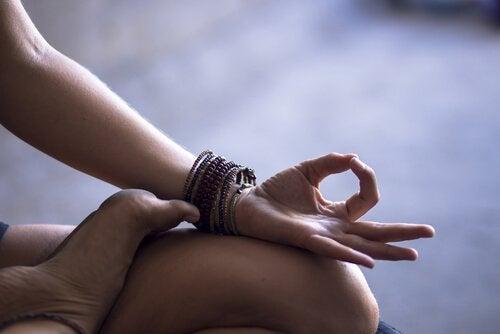 Brazo sobre pierna de una mujer meditando