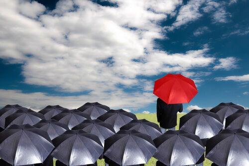 Hombre con paraguas rojo seguido por personas con paraguas grises