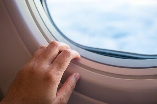 Mano en la ventana del avion