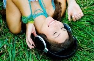 Mujer escuchando música en el césped