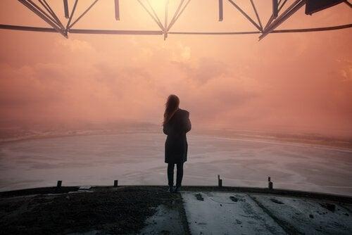 Mujer mirando al horizonte al atardecer