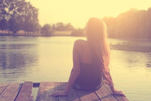 Mujer pensando sentada en un lago