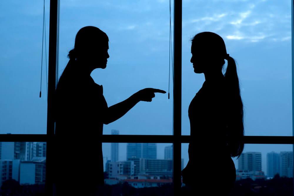 Mujer señalando con el dedo a otra echándole la culpa
