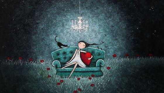 Niña sentada en un sofá agarrando un corazón