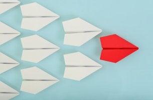 Aviones de papel blanco siguiendo a un avión rojo