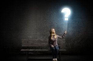 Mujer sujetando una interrogación pensando