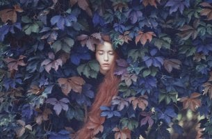 Mujer triste con los ojos cerrados rodeada de hojas