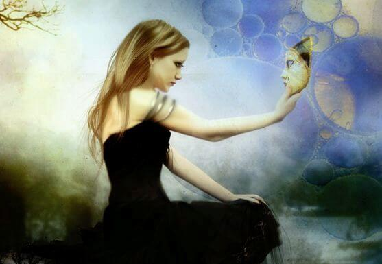 Mujer con una máscara en la mano mirándola de frente