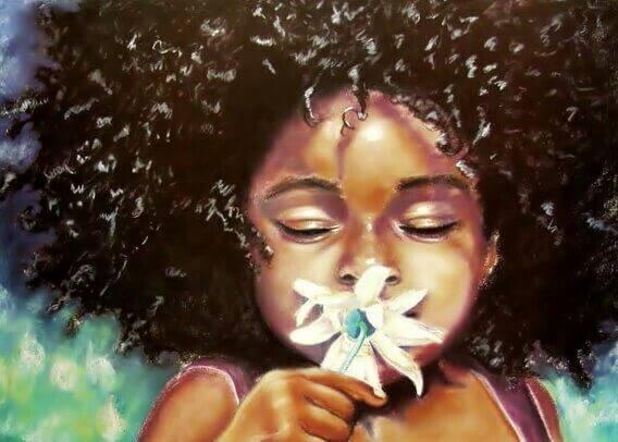 niña de color oliendo una flor