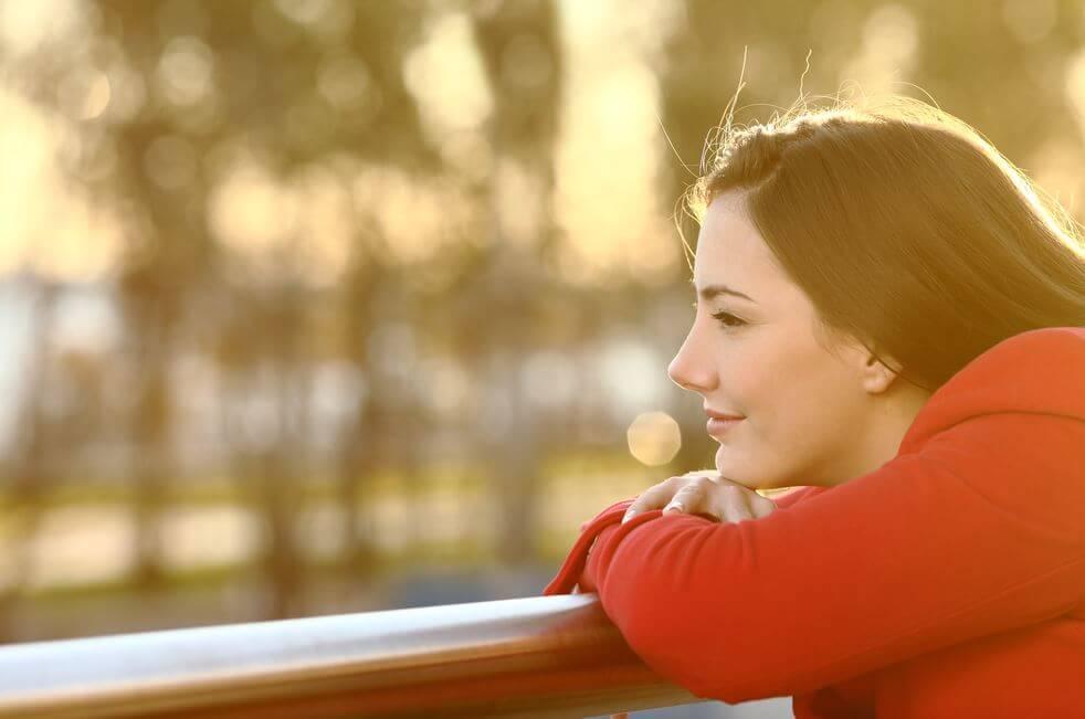 Mujer pensando mirando por un balcón