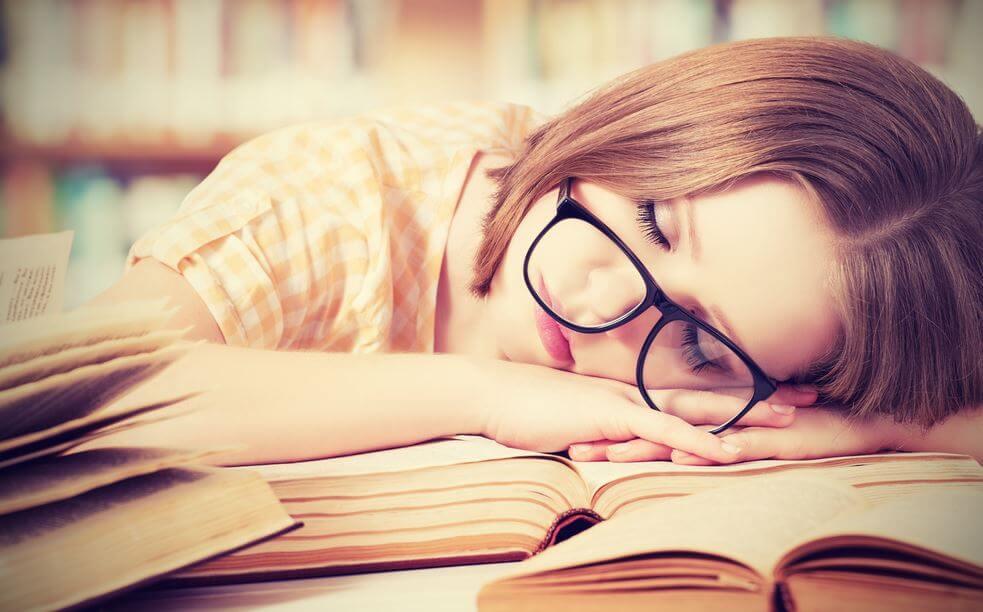 Mujer cansada dormida sobre un libro