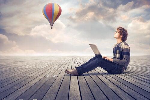 Chico joven con un ordenador pensando en qué quiere trabajar