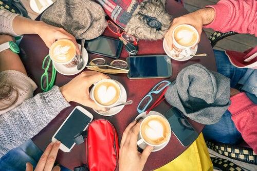 Grupo de amigos tomando café con móviles encima de la mesa