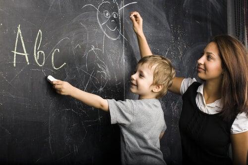 Maestra con niño en la pizarra dibujando