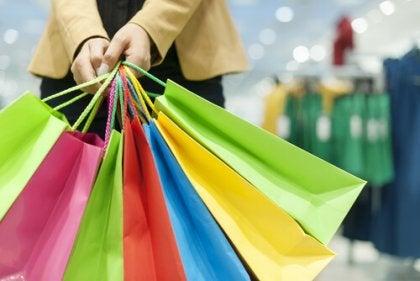 Manos con muchas bolsas de colores