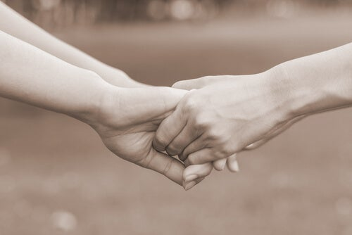 Manos de dos personas agarradas perdonándose