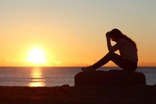 Mujer con dolor sentada al atardecer