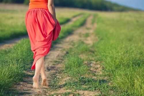 Mujer con falda roja andando por un camino