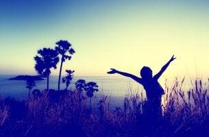 Mujer con los brazos abiertos al amanecer