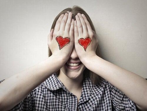 Mujer con corazones pintados en sus manos tapándose los ojos
