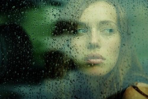 Mujer pensando detrás de una ventana con gotas de lluvia