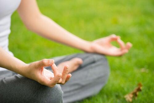 Mujer-sentada-meditando-con-las-manos-apoyadas-en-las-rodillas