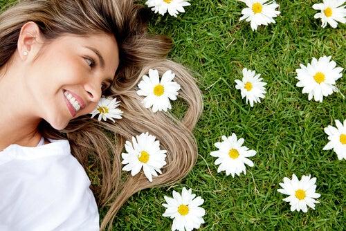 Mujer pensando en su felicidad rodeada de margaritas