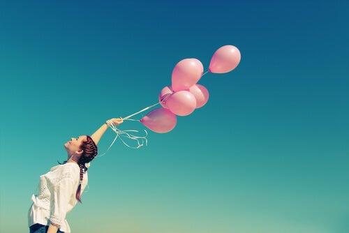 Mujer sujetando globos rosa