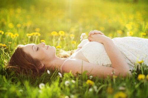 Mujer tumbada en el campo pensando en sus sueños