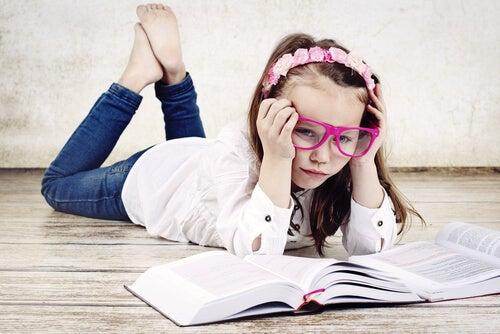 Niña estudiando un libro aburrida