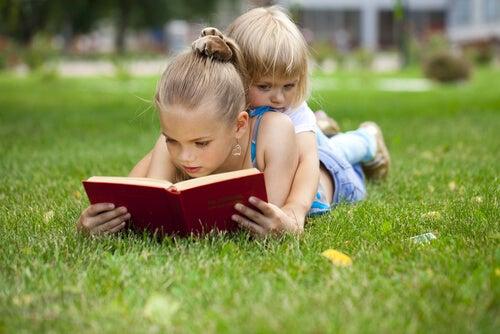 Niña leyendo un cuento con su hermana en el cesped