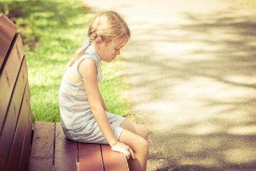 Niña rubia sentada en un banco triste