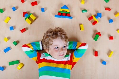 Niño tumbado en el suelo rodeado de piezas de juguetes
