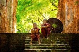 Niños budistas sentados en una escalera leyendo microrrelatos budistas