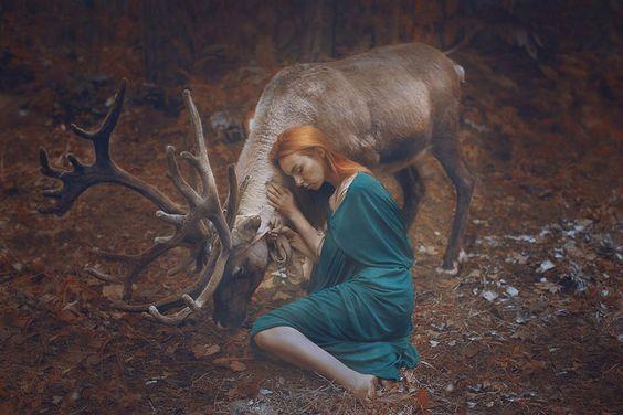 chica con vestido verde abrazada a un ciervo