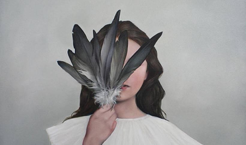 chica tapándose la cara con unas plumas representando la alta sensibilidad